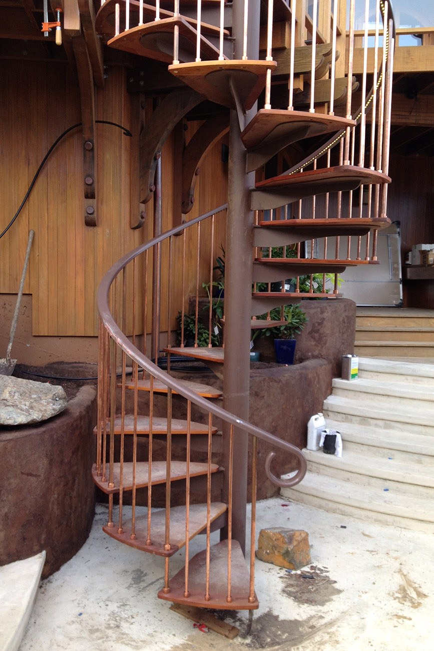 Spiral staircase with H.Mahogany, copper, and inset lighting detail.